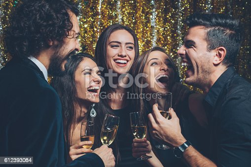 Group of young people in formal wear drinking champagne and laughing at a party.