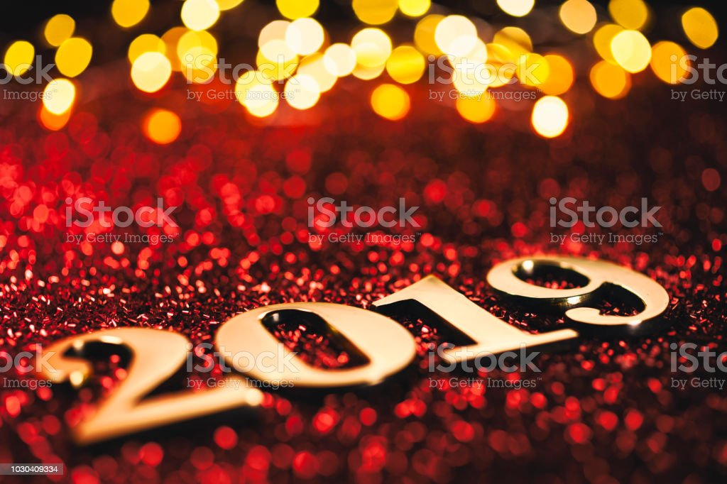 Golden numbers 2019 and Christmas decorations on glitter and...