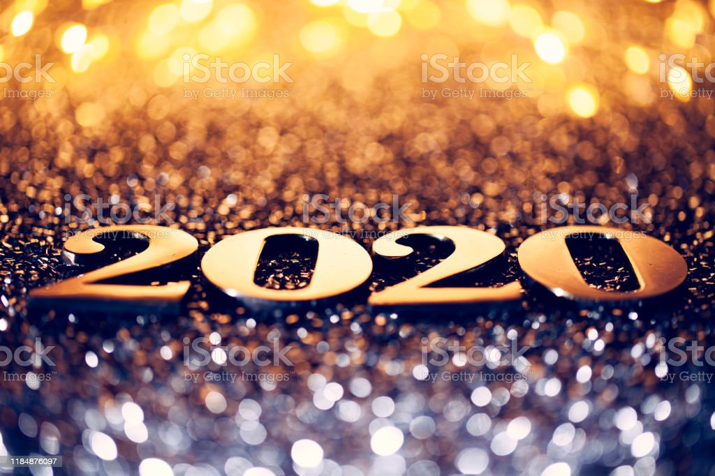 Golden numbers 2020 and christmas decorations on glitter and...