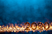 Golden numbers 2020 and Christmas decorations on glitter and defocused lights.