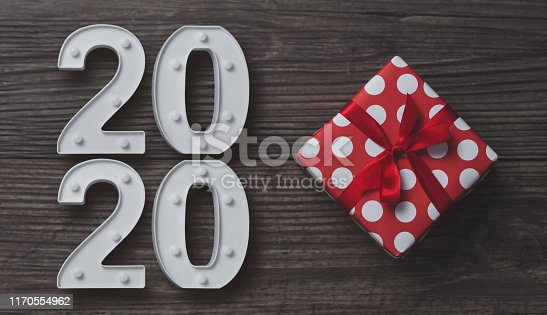 istock New year, Christmas decoration with 2020 and Red gift box on wood background. 1170554962