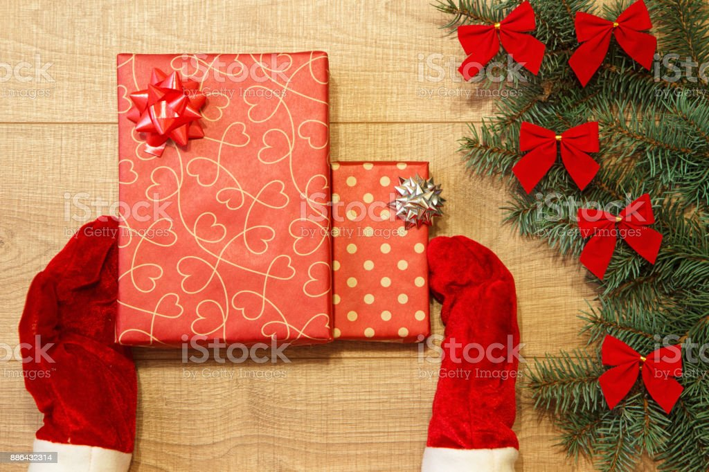 New Year / Christmas gift in package, hands in red gloves and tree with red bows on the wooden background template stock photo