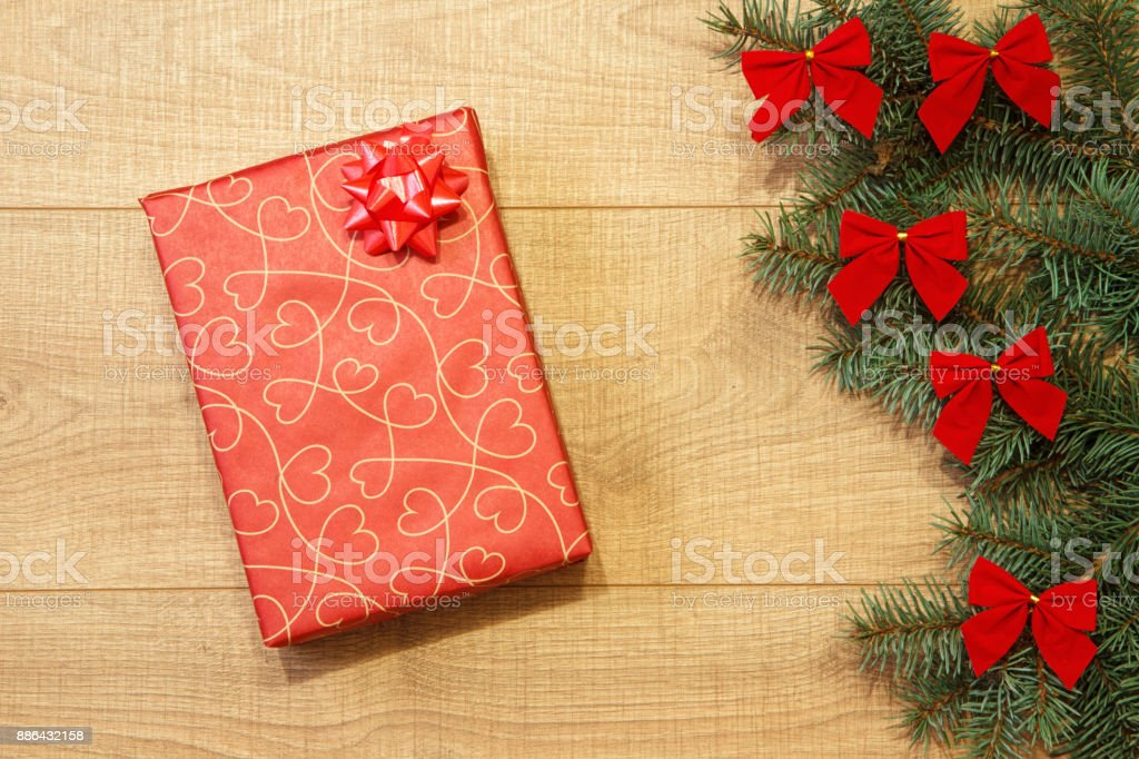 New Year / Christmas gift in package, tree with red bows on the wooden background template stock photo