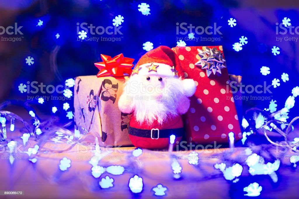 New Year / Christmas gifts in package and blue garland on the wooden background template stock photo