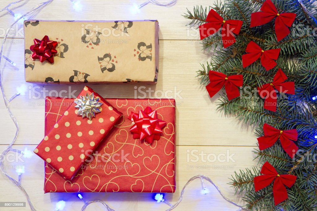 New Year / Christmas gifts in package, tree with red bows and blue garland on the wooden background template stock photo