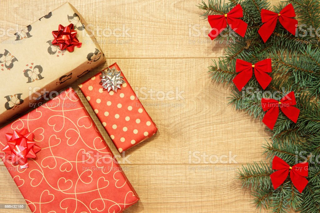 New Year / Christmas gifts in package, tree with red bows on the wooden background template stock photo