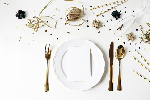 New Year, Christmas styled black and gold table setting with plate, cutlery, confetti stars and champagne wine glass. Party decoration. Restaurant menu blank card mockup, flat lay, top view.