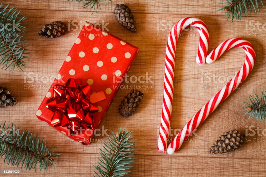 New Year / Christmas tree, cones, gift in package and lollipops on the wooden background template stock photo