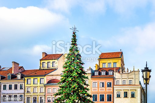 istock New Year Christmas tree decorated with illumination ornaments by multicolored architecture of old town market square in Warsaw, Poland 1284464420
