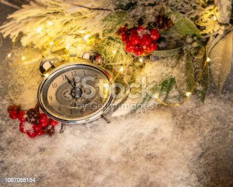 1025550352 istock photo New year clock and cones covered with snow. Christmas and new year's decor 1067055154