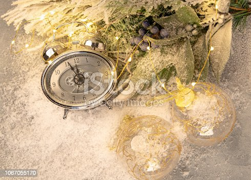 1025550352 istock photo New year clock and cones covered with snow. Christmas and new year's decor 1067055170