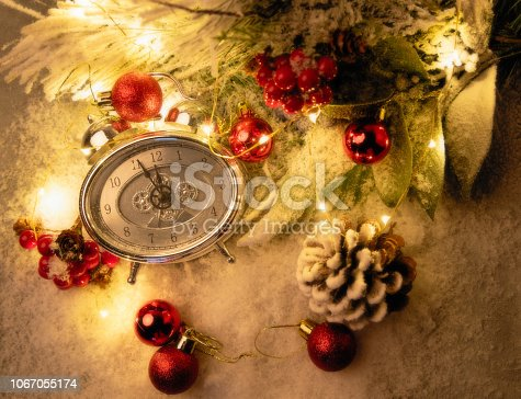 1025550352 istock photo New year clock and cones covered with snow. Christmas and new year's decor 1067055174