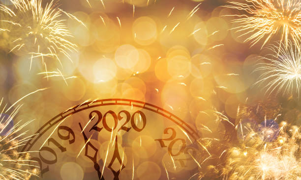 New Year clock near to the midnight of 2020, fireworks golden bokeh background stock photo