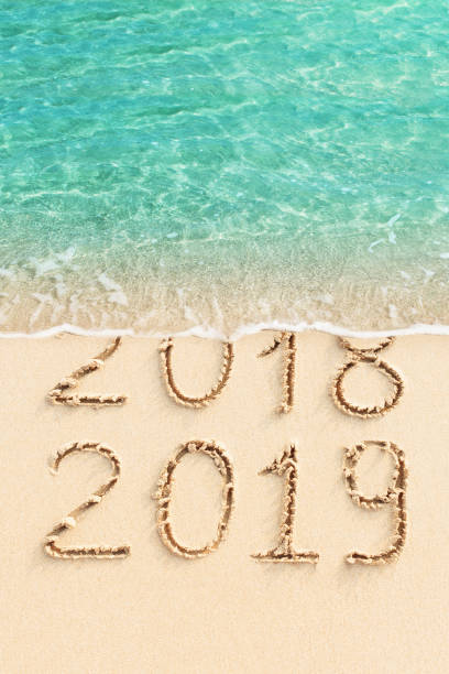 New Year concept - 2018 and 2019 handwritten on the beach stock photo