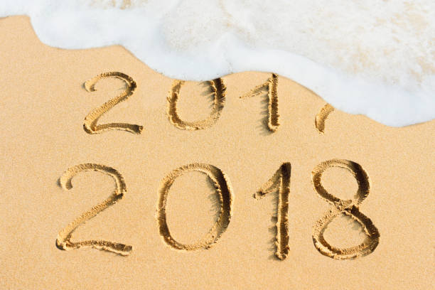 New Year concept 2018 handwritten in the sandy beach stock photo