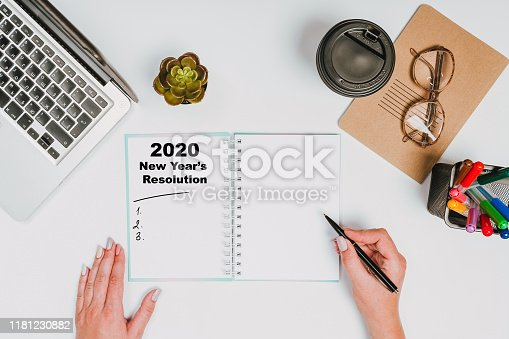 1173922060 istock photo New year Concept - 2020 number and text on notepad and female hands Modern workspace with coffee cup, smartphone, paper, notebook, tablet and laptop 1181230882