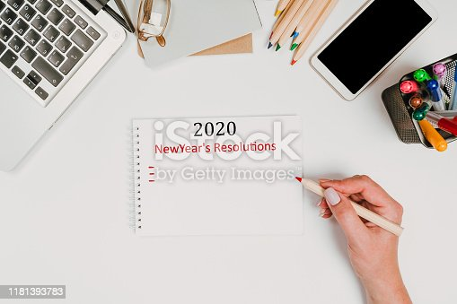 1173922060 istock photo New year Concept - 2020 number and text on notepad and female hands Modern workspace with coffee cup, smartphone, paper, notebook, tablet and laptop 1181393783