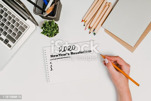 1173922060 istock photo New year Concept - 2020 number and text on notepad and female hands Modern workspace with coffee cup, smartphone, paper, notebook, tablet and laptop 1181588813