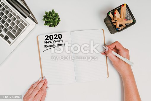1173922060 istock photo New year Concept - 2020 number and text on notepad and female hands Modern workspace with coffee cup, smartphone, paper, notebook, tablet and laptop 1181769897