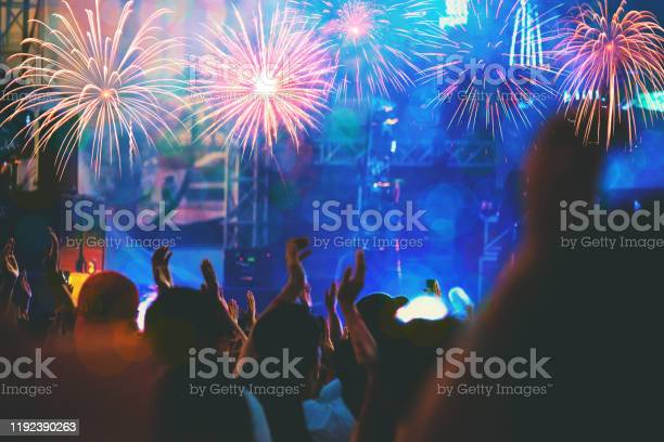 Photo of New Year concept - cheering crowd and fireworks, Group of people having fun at music concert.