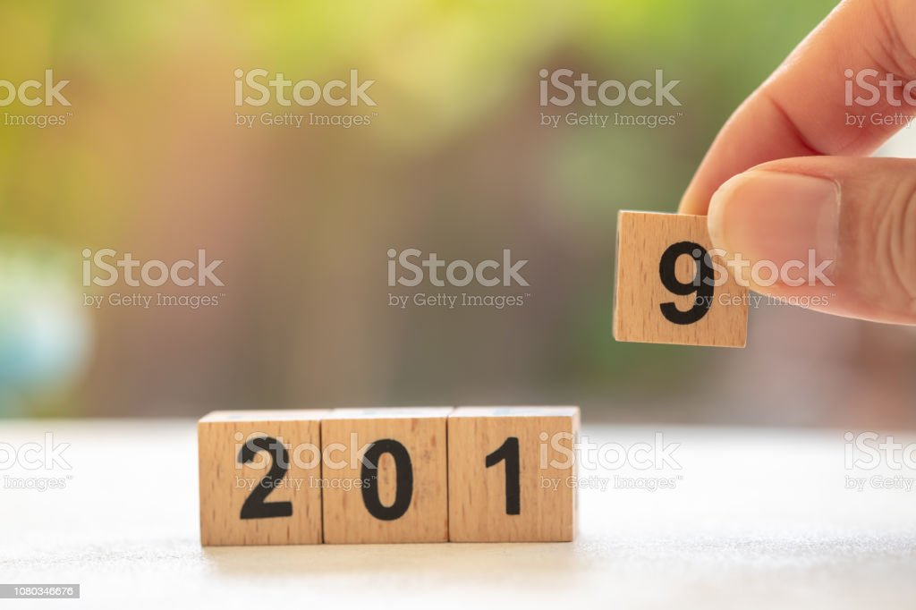 2019 New year concept. Close up of man hand holding wooden block number 9 to fill stack of wooden number blocks stock photo