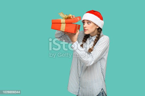 New year concept. cunning beautiful girl in striped light blue shirt in red christmas cap standing holding red gift box, unboxing and looking inside. indoor, studio shot isolated on green background.