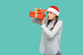 istock New year concept. cunning beautiful girl in striped light blue shirt in red christmas cap standing holding red gift box, unboxing and looking inside. 1026656344