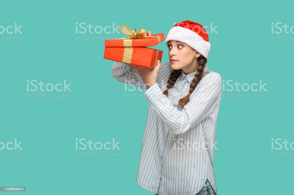 Neujahr-Konzept. List, schönes Mädchen in hellblaues Hemd in Rot Weihnachten Mütze stehende Holding rote Geschenkbox, gestreift, Auspacken und Blick ins Innere. – Foto