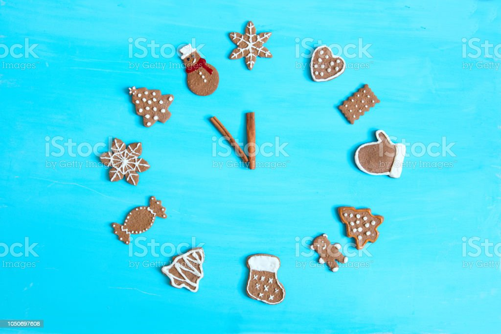 New year concept. Five minutes before the new year. Watch from gingerbread on blue wooden table stock photo