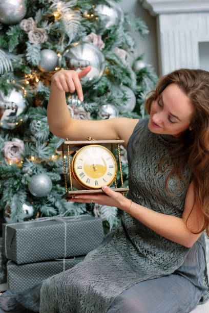 New Year concept - girl shows with a finger a clock. stock photo