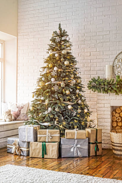 New Year, decorated Christmas tree, Christmas , cozy home interior New Year decorated Christmas tree in a cozy home interior near the fireplace with a clock christmas trees stock pictures, royalty-free photos & images