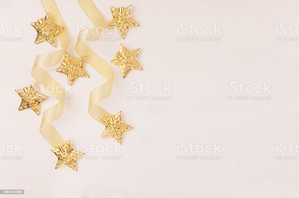 New Year decorations, gold stars and curl ribbon on soft white wooden...