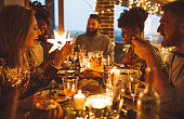 Multi ethnic group of friends having new year dinner party, everyone enjoying in food and drink