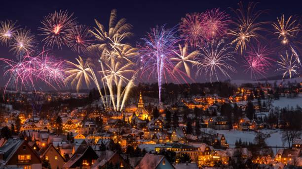 neujahr silvester feuerwerk und beleuchtete häuser in seiffen zur weihnachtszeit. sachsen-deutschland - silvester deutschland stock-fotos und bilder