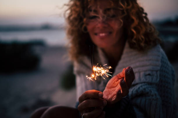 New year eve or celebration time for cheerful lady in the evenign night with fire sparklers - focus on fire and defocused portrait in backgrouind - concept of celebration and romance stock photo
