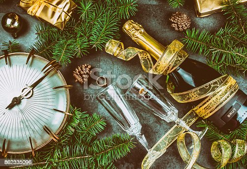 istock New Year Eve tradition rutual put gold ring to champagne. Spanish and Latin American New year traditions. Two champagne grasses, bottle of champagne, vintage clock and Christmas decorations. Top view 862335096