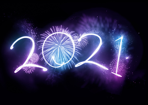 Welcoming the year 2021 displayed with fireworks and strobe lights. New year celebration concept.