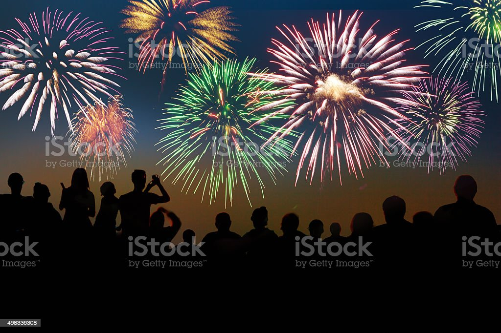New Year Fireworks Exploding Over Celebrating Spectators in Silhouette stock photo