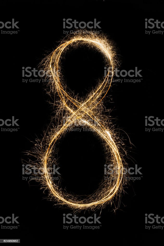 New year font sparkler number eight on black background stock photo