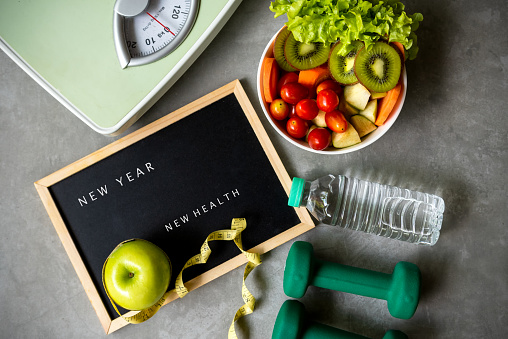 New Year for New Healthy 2021.  Fresh vegetable salad and healthy food for sport equipment for women diet slimming weight loss background. Healthy change new life Concept