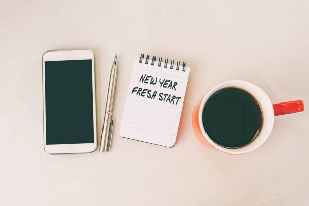 new year fresh start text on note pad with smart phone, pen and cup of coffee - new years day stock pictures, royalty-free photos & images