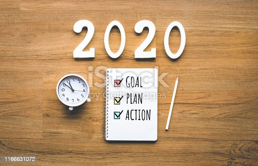 2020 new year goal,plan,action text on notepad on wood background.Business challenge.Inspiration ideas.Human performance