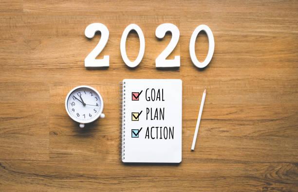 2020 meta de año nuevo, plan, texto de acción en el bloc de notas sobre fondo de madera. desafío empresarial. ideas de inspiración - año nuevo fotografías e imágenes de stock
