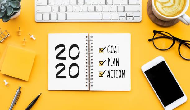 2020年の新年の目標、計画、オフィスアクセサリー付きメモ帳上のアクションテキスト。ビジネスモチベーション、インスピレーションコンセプト - 決意 ストックフォトと画像