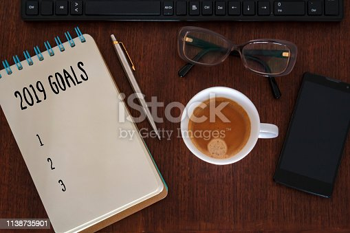 1186985932 istock photo New year goals concept. Office desk with notebook, computer, coffee cup, smartphone and glasses 1138735901
