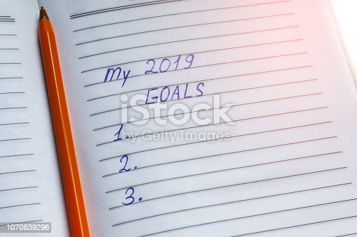 1186985932 istock photo New Year goals handwritten inscription and pen on white striped paper 1070639296