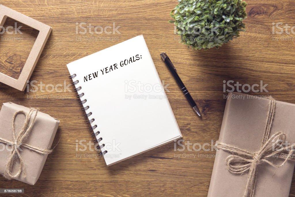 Neujahr-Ziele in Notebook mit Geschenk Box Silvester auf dem Holztisch Hintergrund. – Foto