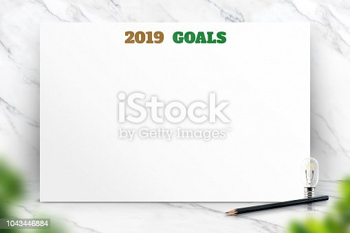 2019 new year goals text on white paper poster and pencil with natural blur leaf foreground on white marble room wall,Business presentation mock up for adding your list
