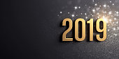 2019 date number colored in gold, on a festive black background, with glitters and stars - 3D illustration