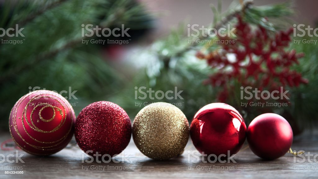 New Year greeting card, Christmas balls in a row, red and gold on a natural background of Christmas tree branches and snowflakes stock photo